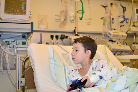 sickroom: Toddler with games console in hospital