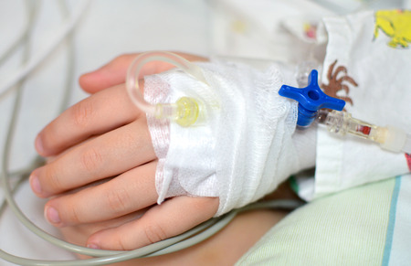 intravenously: small childs hand with an infusion