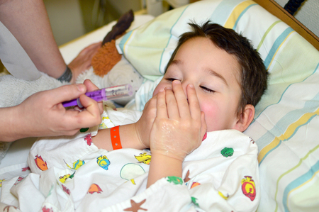 refused: little boy is in the hospital and refused his medicine Stock Photo