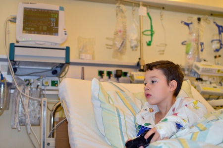 sickroom: little boy playing in the hospital with video games