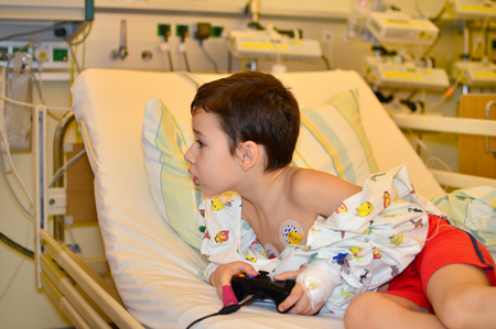 sickroom: little boy playing with a gaming console at the hospital