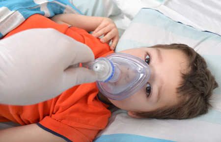 sickroom: little boy with an oxygen mask in hospital Stock Photo
