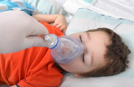 Kleiner Junge unter Anästhesie mit einer Sauerstoffmaske Standard-Bild - 55998802