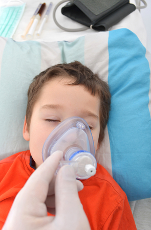 sickroom: little boy under anesthesia with a oxygen mask