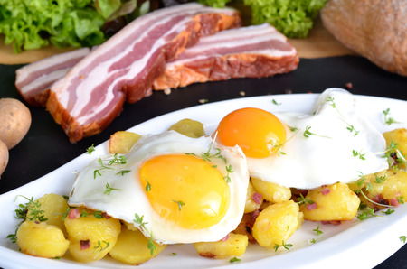 foodstuff: Farmers breakfast, fried eggs with fried potatoes, onions and bacon