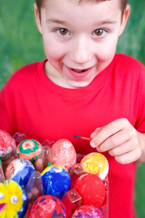 pleasure craft: little boy paints Easter eggs with water colors