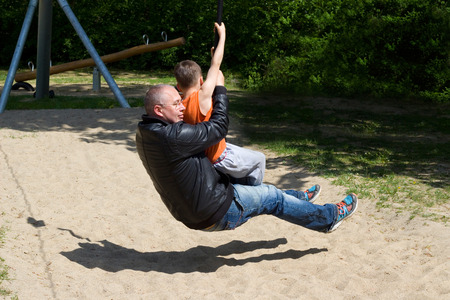 one person with others: Father and son playing on a cable car