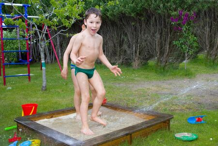 funy: children playing with water in the sandbox Stock Photo