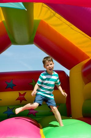 Kleine springt Junge auf einer Hüpfburg Standard-Bild - 61880737