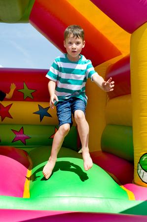 Little jumps boy on a bouncy castle Stock Photo