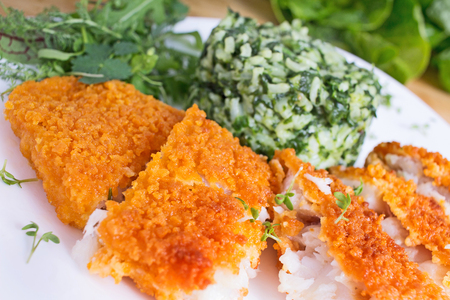 fish fillet: Crispy breaded fish fillet with spinach risotto