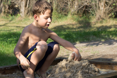 Little boy builds a sand castle in the garden Stock Photo