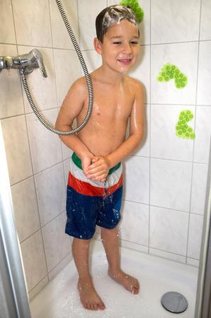 Kleiner Junge steht unter der Dusche stehen und wäscht sich Standard-Bild - 65774504