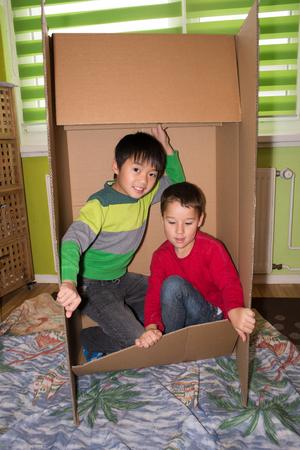children at play: Children play hide in a cardboard box