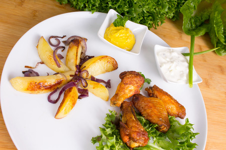Spicy chicken wings with potatoes and various dips Stock Photo