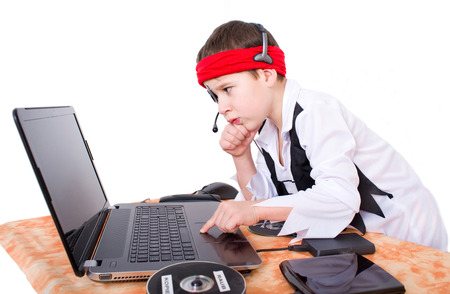 Little boy as a data pirate looks at a notebook Stock Photo