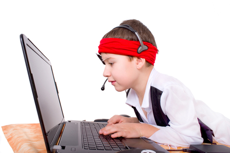 Little boy as a data pirate in front of a laptop