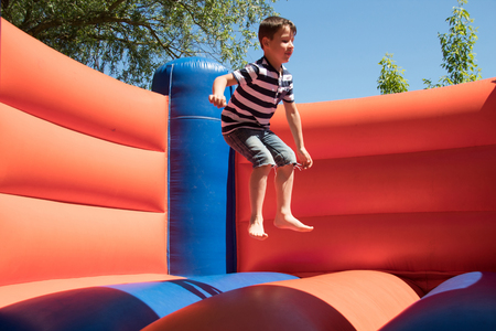 Boy is jumping on a bouncy castle