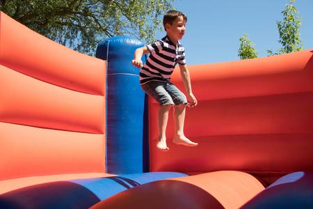 De jongen springt op een springkasteel
