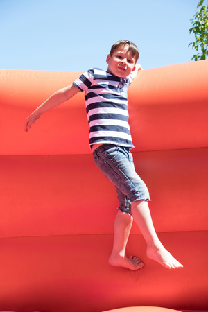 boy is climbing on a bouncy caslte