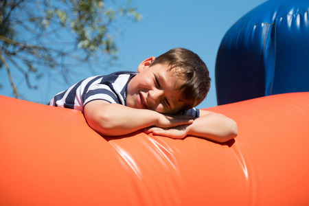 Little eboy is climbing on a bouncy castle Stock Photo