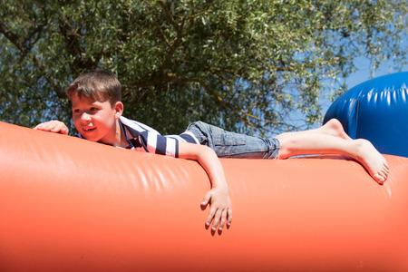 kleiner Junge spielt auf einer Hüpfburg  little boy is climbing on a bouncy castle Stock Photo