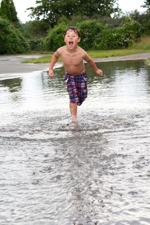 kleine jongen loopt door een peddel