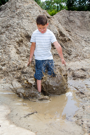 little boy is playing in the mud of a construction site