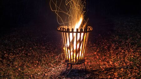 Night shot of a burning fire in a metal basket with leaves on the ground