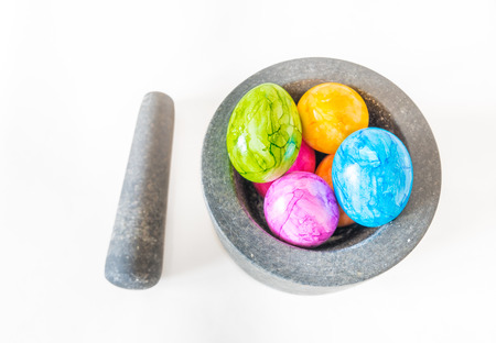 morter: Colorful Easter eggs in a granite mortar and white background