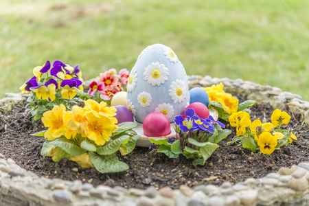 Colorful easter eggs in a flower pot with horned violet flowers