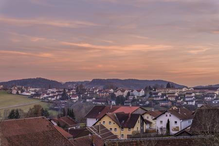 Zachód słońca i wieczorno-czerwieni w bawarskim lesie z widokiem na miasto Grafenau