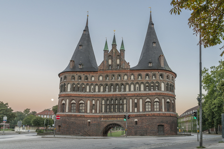Holstentor in Luebeck during sunrise with moon Editorial