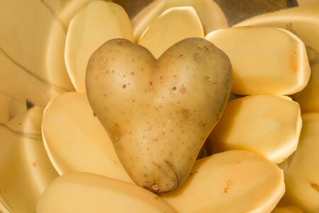 Heart shaped potatoes with other potatos in a bowl