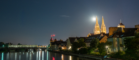 sight seeing: Night shot of Regensburg with moon beside the cathedral Stock Photo