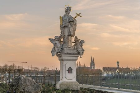 gloriole: Holy statue in Regensburg with dome of St. Peter in the background during sunset