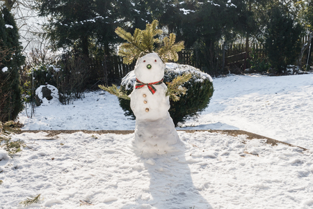 Snowman in the garden at first snow in the winter