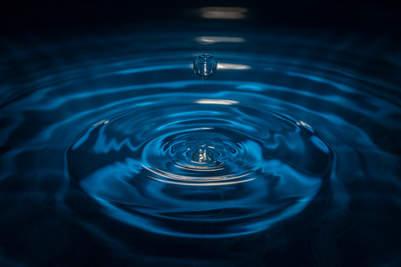 Water drop on waves with blue background and reflection