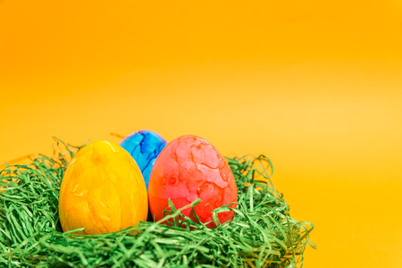 Easter egg in a nest easter made of green grass and yellow background