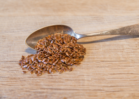 linseed: Silver spoon with linseed on a wooden board Stock Photo