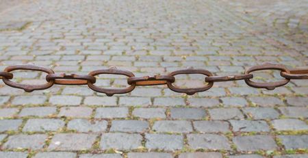 Rusty chain cobblestones in the background Stock Photo
