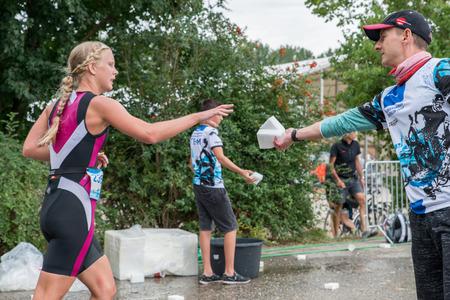 Runner neemt tijdens het hardlopen een plastic spons met water Redactioneel