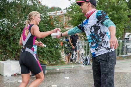 Regensburg, Beieren, Duitsland, 6 augustus 2017, 28ste Regensburg Triathlon 2017, Runner neemt een plastic spons met water tijdens het hardlopen
