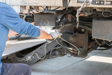 One mechanic is operating a loading ramp of a truck
