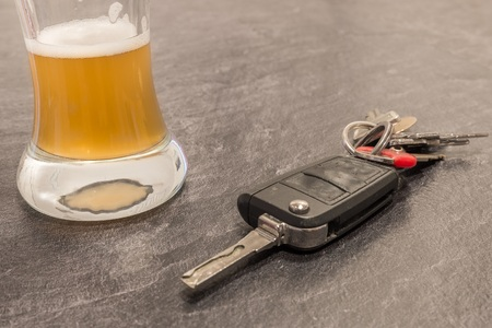 Glass of beer and car key on gray table
