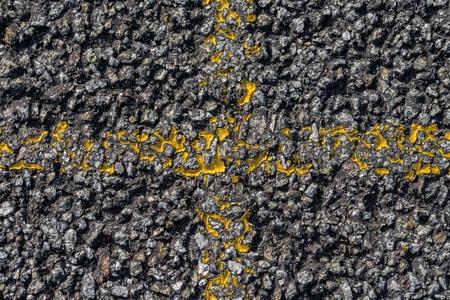 アスファルト上の黄色の十字架 写真素材