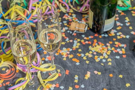 Champagne glass and bottle with carnival decoration on a slate 스톡 콘텐츠