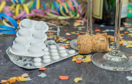 Pills and alcohol with carnival decoration on a slate