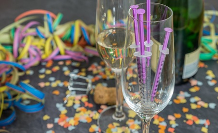 Syringe and alcohol with carnival decoration on a slate