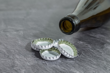 Bottle cap with a beer bottle on a slate